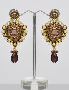 $18.00  Save:50% off  Be the center of attraction in any party/function wearing this gorgeous looking design & latest fashion, beautiful pair of Polki earrings with famous Indian craftsmanship. Set on golden one, earrings are adorned with shining white & light & dark mauve/purple color stones, kundan and pearls all over finished with crystal drop. Steal the limelight with this pair of Polki Earrings!! Length of the earrings is 3 Inches