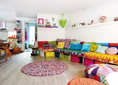 Pretty bright boho chic living space. Love that expansive lounge with practical storage underneath. Great family space!.