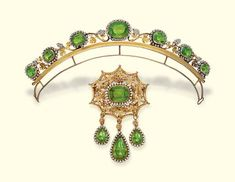 AN ANTIQUE PERIDOT AND SEED PEARL DEMI-PARURE   The tiara designed as a graduated line of cushion-shaped peridot and pearl clusters to the pearl berries with gold filigrée vines and leaves, brooch en suite with three detachable pear-shaped drops, mounted in gold (one paste replacement in tiara), circa 1830, tiara 20.5 cm. wide, brooch 9.0 cm. high