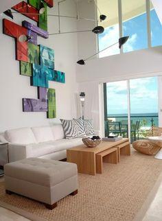 Living Room by poggi design | tetris wall art | sisal rug | high ceilings | big windows | white sofa | natural wood coffee tables |