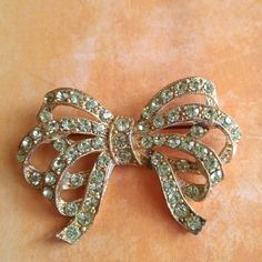 Vintage bow brooch pot metal green rhinestones Lovely vintage bow brooch made of sage green sparkly rhinestones set in gold plated pot metal True vintage from about 1940s In very nice condition with light surface wear Unsigned From a smoke free home Vintage Jewelry Brooches
