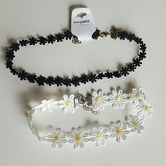 Double choker necklace bundle! These two lovely choker necklaces are very cute and detailed each petal is beautifully made and attached to  clips and aditional chain will allow for the perfect fit! White and yellow daisy flower and adorable black mini daisy flower. Great with your favorite shirt and jeans. Jewelry Necklaces