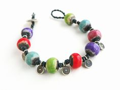 Spice of Life Bracelet - fun and colorful bracelet tutorial using 12mm round beads and spiral pewter charms.  Find your bead needs at www.happymangobeads.com