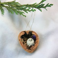 Handcrafted Christmas ornament of a miniature owl nesting in a half walnut shell.