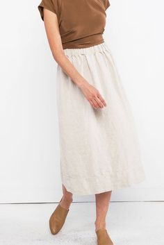 Neutral midi skirt, cognac/umber colored shirt, tan mules