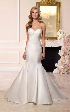 This stunning Dolce satin fit-and-flare wedding gown from Stella York features a beautifully-beaded lace bodice, and gorgeous lace detailing on its train.
