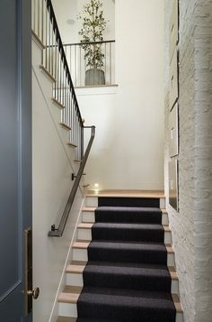 Staircase with exposed brick painted in white and custom railings. #Staircase #ExposedBrick #Stairs #Railings Jackson and LeRoy