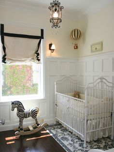 Board and batten, white iron crib, rocking zebra, dark wood flooring, hot air balloon hanging from ceiling. Could work as boy or girls nursery.
