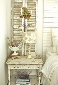 Shabby chic bedroom with weathered shutters behind bedside table and rustic decor.