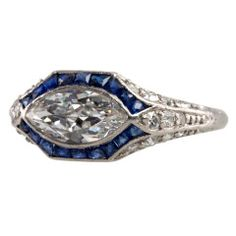 This platinum ring is for that person who wants something a little less traditional, but beautiful! The center diamond is an approximately one carat I-VS2 bezel set old cut marquise diamond, set horizontally, and surrounded by a channel of french cut sapphires! There are three fingers of single cut diamonds up each side with beautiful engraving and gallery work. Circa 1920 #CraigEvanSmall #AntiqueEngagementRings