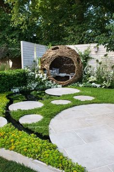 woven willow bird hide (willow sculpture) and concrete circular slabs as a path over a pond surrounded by Chamaemelum nobile (chamomile lawn), Eryngium giganteum, Eremurus himalaicus:
