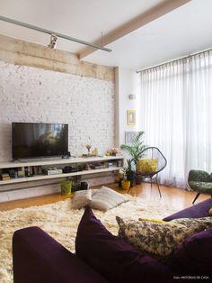 Truques para uma sala super aconchegante: tapete fofinho, sofá confortável com muitas almofadas, cortina esvoaçante até o chão e parede de tijolinhos.