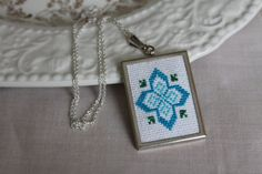*** CLEARANCE ITEM: DESIGN DISCONTINUED ***  Pendant is hand stitched with cotton embroidery floss in dark and light blue with green accents.