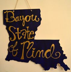 "Louisiana State MDF Cutout with a dark blue background the saying ""Bayou state of mind"" in gold door hanger and home decor"