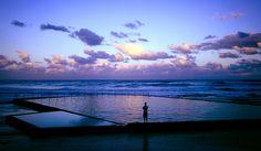A lone figure contemplates the beauty of sunset.  Wombarra sea pool, NSW Australia