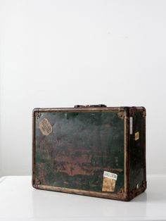 This is vintage pre-1960s metal suitcase with 1960s era stickers. The old metal trunk case features forest green metal with brass tone trim and fixtures. It has a black plastic handle. Loads of sticke