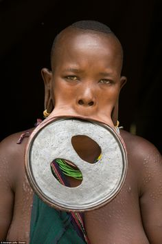 Ataye Eligidagne, 20, dons the largest lip disc in the world. The hardened clay disc is 59.5cm