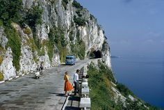 Motorists pass people on a scenic road atop a cliff overlooking a bay near Trieste, Italy, 1956.Photograph by B. Anthony Stewart