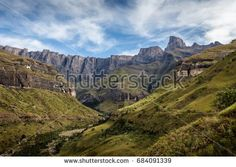 Royal Natal National Park, KwaZulu-Natal, South Africa - May 16th, 2015. View of the Amphitheatre, geographical feature of the Northern Drakensberg in South Africa. mountains, drakensberg, amphitheatre, south africa, african, travel, natal, landscape, landmark, nature, green, grass, blue, sky, beautiful, clouds, peaks, rocks, park, valley, water, hiking, outdoors, tourism