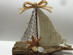 This sailboat is made out of driftwood that I found on the beach. The sails are made out of fishnet and burlap. This sailboat is 12 inches long and 11 inches high.