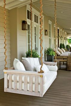 This plush white porch swing provides extra seating for this spaciouswrapped covered porch—perfect for entertaining.    Tour the Nashville Idea House