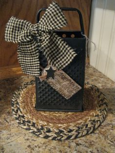 Spray paint an old grater with black paint and use rosemary for greenery and bow.