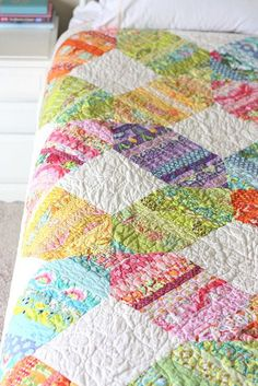 """scrappy modern quilt by amy smart; joining blocks are called """"quarter square triangles""""."""