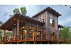 Exterior view of the home with wrap-around deck.  Contemporary mountain house with Green materials.  Recycled Wyoming snow fence wood siding, wood rainscreen, and shed roofs.