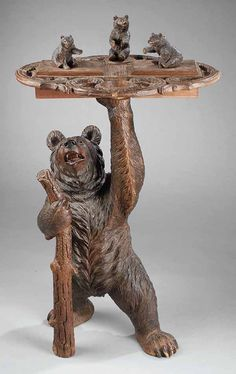 An Interesting Black Forest Carved Walnut Smoking Stand, late 19th c., the scalloped branchwork carved swivel top with three bear cubs and hinged containers above a large standing bear hinged container, with glass eyes and clutching a tree branch, height 37 1/2 in., width 21 in ., depth 17 in