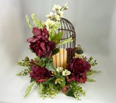Bird Cage Floral Arrangement, Flower Centerpiece, Wedding Centerpiece  A beautiful Bird Cage Arrangement that will enhance any room in your home. Use it sitting or it can even hang from a hook. I accented this bird cage with burgundy peonies, ivy, astilbe, boxwood, ivory, sage green and mauve flowers and a cute little bird. Inside is a vanilla scented flameless candle with a timer, 6 hours on and 18 hours off, it uses 3 AAA batteries that are included. All of my designs are one of a kind…