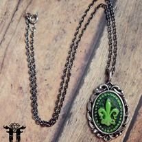 """This awesome necklace features a custom made and hand painted by me Fleur de Lis cameo! The pendant measures approximately 1.75 by 1 inches. It is nicely displayed on a 17"""" gunmetal chain necklace!"""