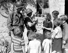 à Trévières une femme et ses enfants échangent quelques mots avec deux GI'S. (Photo US Signal Corps).
