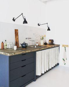 Com a predominância do branco no ambiente, dá para investir em móveis com cores mais chamativas, como essa bancada laqueada em azul petróleo e tampo em concreto.