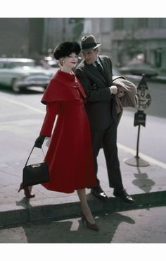 Gretchen Harris walking on street with man, wearing crimson coat with high waist buttoned-on cape by Young Couture, fox hat by Emme, purse by Kore  Glamour September 1956 © Sante Forlano