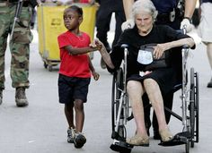 A five-year-old girl holds hands with a 105-year-old woman as they are evacuated from the convention center in New Orleans following on from the infamous hurricane