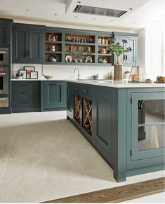 The beautiful bespoke island features integrated wine storage and a combination of open and closed s Dark Green Kitchen, New Kitchen, Green Kitchen Island, Green Kitchen Interior, Closed Kitchen, Kitchen Chairs, Kitchen Decor, Kitchen Layout, Tom Howley Kitchens
