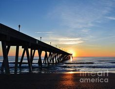 "This beautiful scene of the ""1st Sunrise Of 2015'' was photographed by Bob Sample of PKS Images at Mercers Pier on Wrightsville Beach NC as the sun was making it's first appearance of the new year. With the wispy clouds and the reflection of the sun cascading across the waves to shore, it was a very peaceful and calming way to usher in the new year."