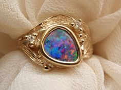 Very colorful boulder opal from all angles and directions (looks like fine black opal). 3.49 grams of 14k yellow gold surround this boulder opal doublet weighing 1.04ct flanked by a diamond at either side weighing .06TCW.