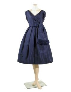 Christian Dior Blue Taffeta Evening Dress   French, late 1950s   The fitted draped bodice made over a tulle foundation, V-neckline, set in short sleeves, the controlled box pleated skirt made over three tulle petticoats, focal point of wide fringed streamers from faux side surplice closing, size 6