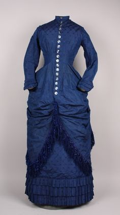 Dress Accession Number: 1996.24.137-A-B Date Made: 1878-1879 Description: Dress; two piece, royal blue embroidered silk, bodice is tunic style with bustle and blue silk fringe around hem; sleeves and skirt have three rows of pleats at hem. Bodice (A), narrow banded collar with center front button closure; seventeen buttons painted in blue and white with red paisley motifs.