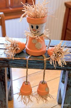 """This little straw man is just too cute to be scary. To make him, embellish a set of clay pots with bits of burlap, strands of raffia and simple acrylic paint for the face. When everything is dry, thread four extra long strands of jute twine through the head, knotting them together on the inside. Let the """"arm"""" strings dangle to the sides, and thread the """"leg"""" strings through the upturned body. Then, knot on the hands and feet as shown."""