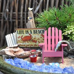 At The Beach  Create a beach scene with clear blue stones, a sandy beach and a small piece of 'driftwood'. Add a white picket fence and a post for seagulls to perch and hang a beach sign. Complete the beach scene with a Adirondack chair of your favorite color, a bucketful of seashells, and a beach towel.