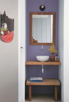 O lavabo se divide em duas áreas separadas: dentro, fica o sanitário e, aberta, do lado de fora, a pia encaixada em um recuo, solução que permite o uso simultâneo dos dois espaços. A pintura roxa e a bancada de madeira conferem personalidade.