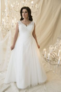 A line silhouette with a pleated tulle overlay and lace detail on the waist sleeves and over the bust. Full corset bodice and scallop edge lace on the neckline.