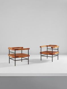 ROBERTO GABETTI AND AIMARO ISOLA  Pair of armchairs  1956  African teak, ash, leather, painted steel.  Each: 27 x 28 x 28 in. (68.6 x 71.1 x 71.1 cm)  Produced by Colli, Turin, Italy. From the production of 4. Undersides incised III and IIII, respectively. Underside of one with foil manufacturer label printed Colli/TORINO.