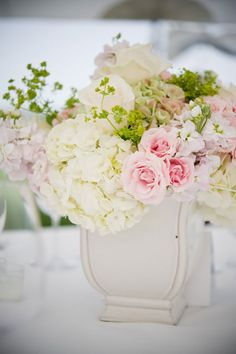 The rest of the tables will have square vases wrapped in ti leaves overflowing with white hydrangeas, green sage leaves, blush pink spray roses and white cymbidium orchids.