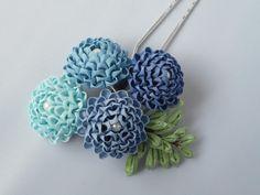 つまみ細工の簪です。絹を様々な青に染めてお花を制作しました。葉も自分で染めています。染めた青の布を小さくカットして細工しました。さわやかな青を集めた簪です。
