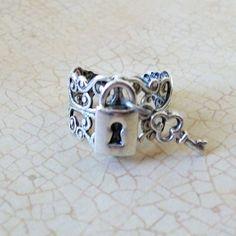 Un petit fermoir en argent vieilli et une clé sont montées sur un anneau réglable filigrane plaqué argent vieilli. Nous utilisons maintenant un