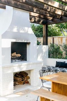 Under a dark stained pergola, a white fireplace is fixed over white brick firewood storage. Under a dark stained pergola, a white fireplace is fixed over white brick firewood storage. Outdoor Space, Outdoor Rooms, White Fireplace, House Exterior, Fireplace Design, Pergola Plans, Rustic Outdoor Decor, Backyard Fireplace, Outdoor Design