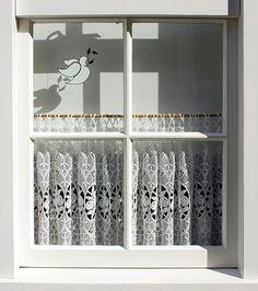 Ventana con visillos bordados en una casa de Marken